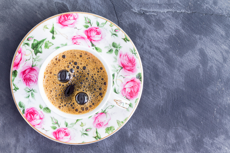 energising: Cup of strong black Turkish coffee in a pretty porcelain cup with pink roses viewed from above on a slate background with copy space Stock Photo