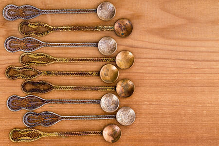 ornately: Row of nine ornately decorated antique historical Turkish Ottoman era tea spoons with copy space over smooth wooden cedar background