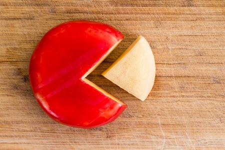 Wheel of verse Goudse kaas met een rode schil en een enkele wig gedeelte uitgesneden, geschild en gescheiden aan de kant op een houten snijplank Stockfoto