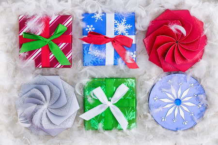 padding: Top down view on six Christmas gift packages surrounded by fluffy padding that resembles snow or white feathers