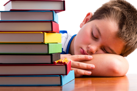 classwork: Bored or overworked schoolboy asleep on his desk alongside a huge stack of colorful text books in a conceptual image Stock Photo