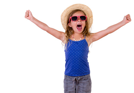 Trendy pretty little girl in a summer outfit , sunglasses and straw hat raising her arms and cheering, three-quarter isolated on white