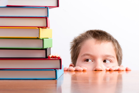 peeping: Thoughtful young schoolboy eyeing up his books peeping over the top of his desk at a huge stack of colorful hardcover textbooks