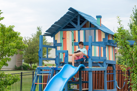 hobby hut: Happy little boy in shorts seated comfortably in chair on freshly painted outdoor personal playground with slide and ladders