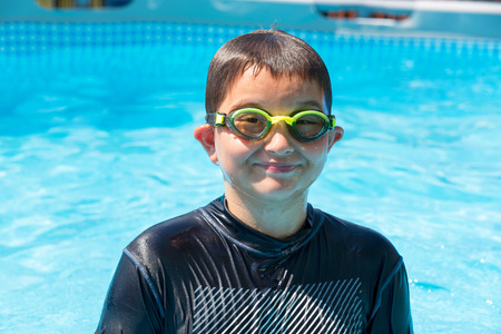 Soaked single grinning boy in swim shirt and goggles at outdoor swimming pool during summer season 스톡 콘텐츠