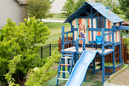 Excited child in bathing suit waving arms while standing on top of newly painted outdoor recreation playground with swing, slide, handlebars, chair, door and window Stock Photo