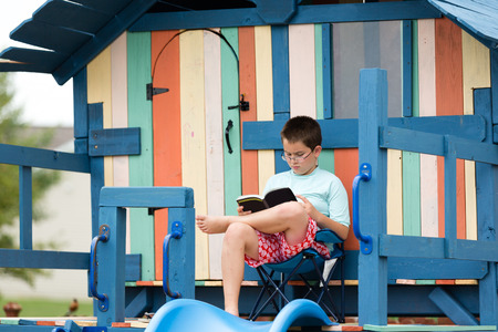 Young twelve year old boy sitting reading on a wooden playground made from colorful stained wood as he enjoys his summer break