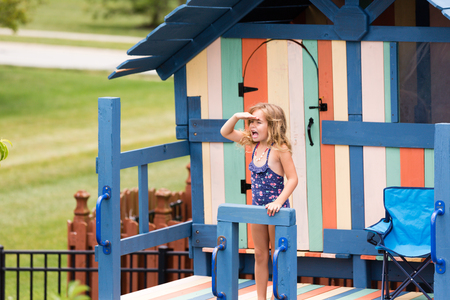 playhouse: Cute little girl with hand over eyes shouting to someone from outdoor recreation playhouse with handlebars, chair, door and window