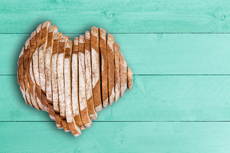 Top down view on sliced bread loaf shaped as heart over wooden table surface with painted green panels and copy space