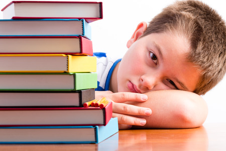 unmotivated: Depressed young schoolboy eyeing his textbooks piled in a huge stack alongside him as he rests his head o the desk while looking at the camera