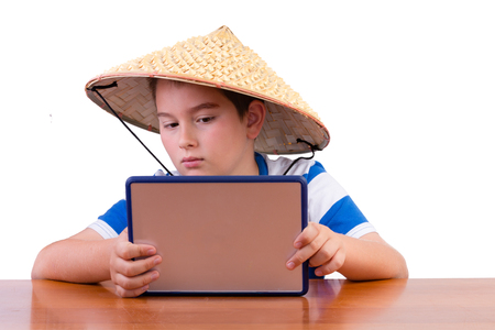 he is a traditional: Young schoolboy studying in a traditional straw Chinese hat holding up a tablet in his hands as he reads the screen while seated at a table