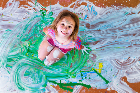 splattered: Creative paint splattered little girl having fun with paints kneeling in the center of her artistic modern painting grinning up at the camera, overhead view Stock Photo
