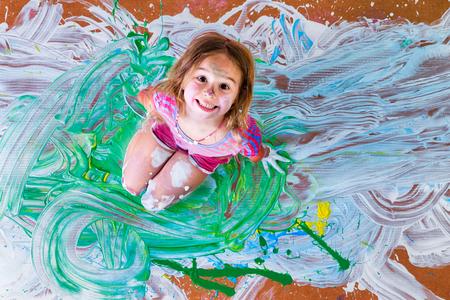 Kreative Farbe bespritzt kleines Mädchen, das Spaß mit Farben im Zentrum ihres künstlerischen modernen Malerei kniend in die Kamera grinsend, Draufsicht