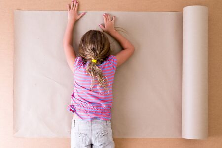 creative artist: Depressed young little girl artist lying face down on the paper as she struggles to come up with original ideas and creative designs, overhead view