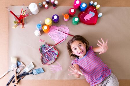 playful: Playful little girl surrounded by her jars of colorful watercolor paint and brushes lying on a sheet of brown paper looking up at the camera with a fun expression and hands outstretched, overhead view