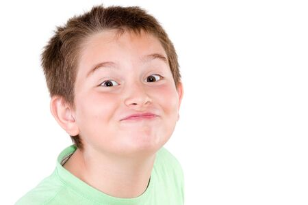 impish: Playful mischievous young boy pulling a cute funny face at the camera with a jaunty look, head shot isolated on white