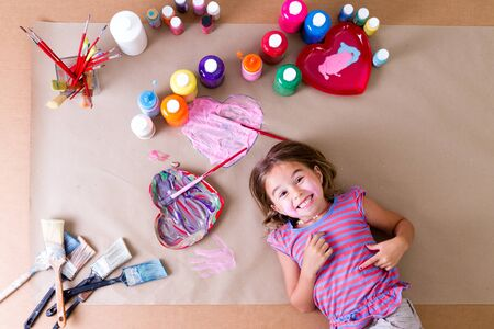 Happy cheeky little girl artist with her art supplies lying surrounded by colorful jars of paint, brushes and pretty heart designs on a sheet of brown paper grinning at the camera, overhead view