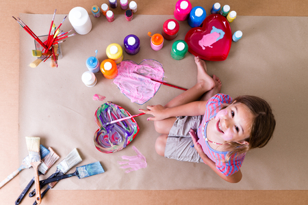 Pretty creative little girl artist kneeling on brown paper with her paints and brushes and colorful heart designs looking up at the camera with a happy grin 스톡 콘텐츠