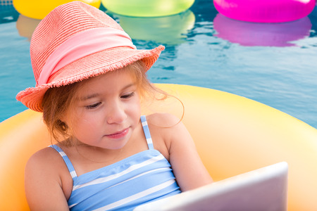 preoccupied: Single cute little girl in hat and blue and white swim suit using laptop while in swimming pool pool Stock Photo