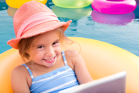 bashful: Smiling blond girl floating on yellow inner tube beside other pink and green devices on a sunny day