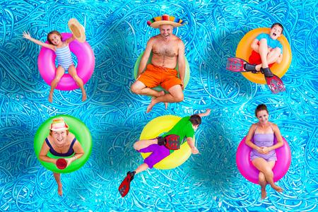 Family fun dans la piscine en été avec un père, mère, grand-mère, les garçons et une fille flottant sur tubes intérieurs colorés dans leurs maillots de bain dans des positions Vaus, image conceptuelle Banque d'images