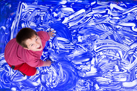 Cute single laughing boy in red shirt splashing hands in blue paint for abstract mural Imagens
