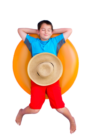 Cute barefoot young boy relaxing on a colorful bright orange inner tube or floaty with a straw sunhat on his stomach isolated on white conceptual of a summer vacation Фото со стока