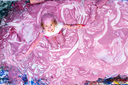 daubed: Single excited cute five year old girl with outstretched arms playing in gobs of pink paint on floor Stock Photo