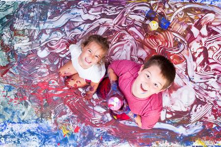 Bonne fille et un garçon regardant tout en partie recouverts de peinture de fresque qu'ils font avec leurs mains Banque d'images - 61807405