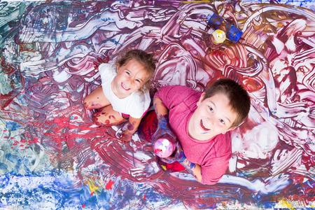 Happy girl and boy looking up while partially covered in paint from mural they are making with their hands