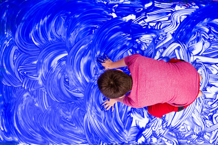 smearing: Top down view on boy smearing hands in blue paint over white canvas paper on floor