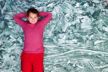 smeared hand: Cute grinning pre-teen or tween boy in red shirt relaxing and lying down on large green smeared hand painting Stock Photo