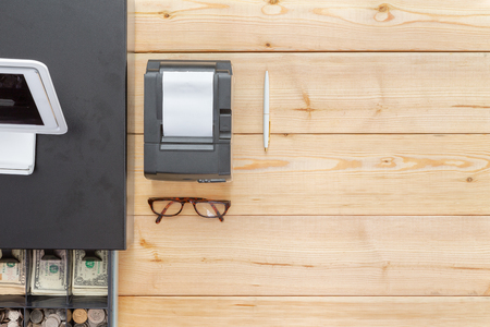 Business cash register on a clean wooden desk or counter with an open cash drawer showing American currency and a pair of folded spectacles, overhead view wit copy space
