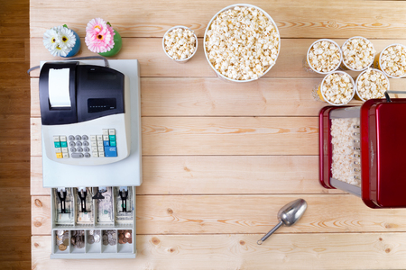 popcorn bowls: Bowls of fresh popcorn alongside a till or cash register with an open drawer displaying American dollar banknotes and coins and a popcorn making machine alongside conceptual of sales, overhead view