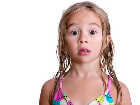 petite fille maillot de bain: Surpris ou inquiet seule petite fille en maillot de bain rose et bleu avec de longs cheveux blonds humide sur blanc Banque d'images