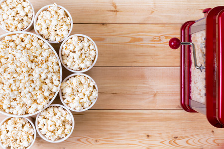 Dishes of fresh popcorn arranged in a decorative circle around a larger center bowl alongside a machine on a wooden table with copy space Standard-Bild