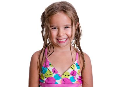 Glückliches kleines Mädchen in niedlichen rosa und blauen Badeanzug mit toothy Lächeln und nassen Haaren auf weißem Hintergrund