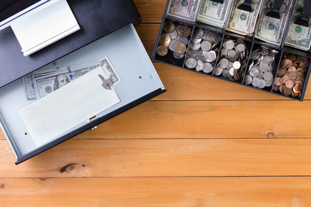 takings: Top down view on separate cash drawer stocked with coins and American dollars beside open register with key and large denomination bills on wooden table. Includes copy space.