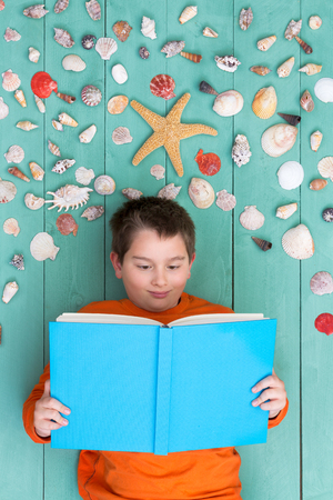 book concept: View from above on cute boy with large blank hardcover book laying down near spaced out assortment of seashells on green wood for concept about imagination Stock Photo