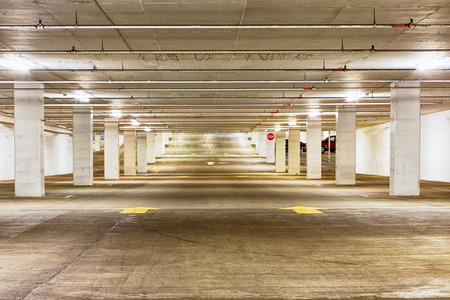 undercover: View looking down the length of an empty undercover parking garage illuminated by overhead strip lights with forward pointing arrows on the concrete floor