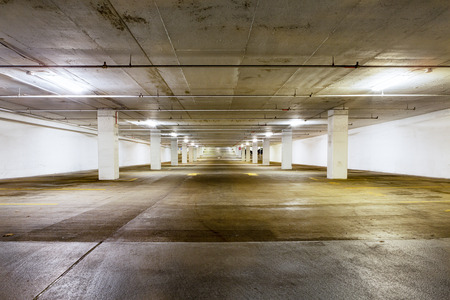 undercover: Large grungy empty undercover parking area viewed down the length with receding perspective lit by overhead strip lights