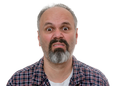 wide eyed: Middle-age man with a goatee with Monday morning blues standing in his pyjamas pulling a wide eyed disgruntled face of mock horror, head and shoulders on white Stock Photo