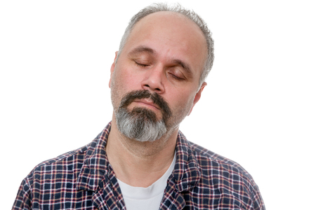 somnolence: Dozy bearded middle-aged man early in the morning standing with his head tilted to the side and eyes closed with a lethargic expression