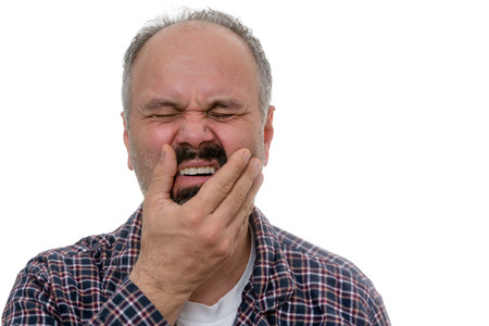 Middle aged man woke up with toothache, holding his shicks with a painful facial impression