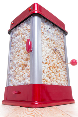 Low angle view on red and gray full popcorn maker on table with handle and white background Stock Photo