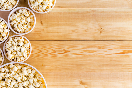 popcorn bowls: Movies background with various sized full popcorn bowls on table from top down perspective