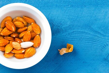 Top down view on whole raw almonds soaked in water over blue wooden table surface. Includes peeled nut skin and copy space.