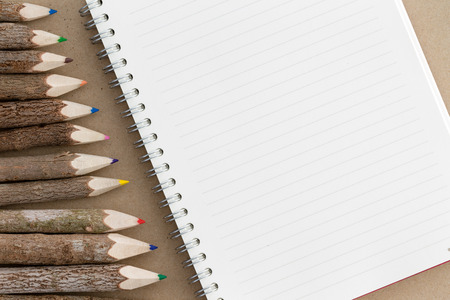 ruled: Spiral bound notebook with a blank ruled page with copy space alongside an angled border of rustic natural wood colored pencil crayons, overhead view