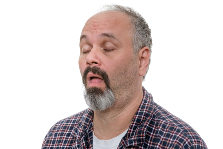 unwinding: Balding man with beard and plaid shirt snores with eyes closed against a white background