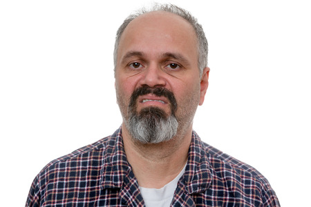 derision: Disgusted man with beard makes face at camera while wearing plaid shirt